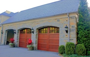 Stone garage addition with custom wooden doors